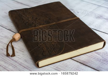 Classic Leather Bound Journal Book on a White Barn Board Floor Close Up