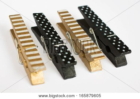 Four Gold And Black Clothes Pins With Fun Patterns Perspective View