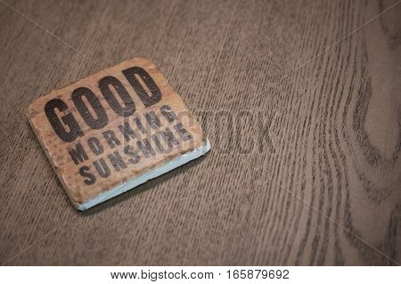 A stone coaster on a wooden table surface reading Good Morning Sunshine