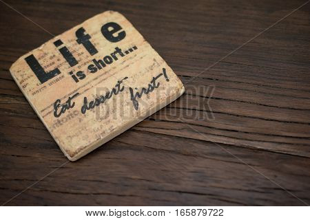 A stone coaster on a rough wooden table surface reading Life is Short...