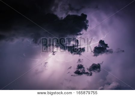 Lightning Bolt Discharges In Purple Storm Clouds At Night Close Up
