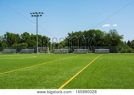 Soccer Field With Bleachers And Light Stand On A Sunny Day