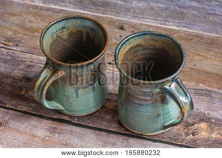 Two Rustic Clay Mugs on a Old Barn Board Floor