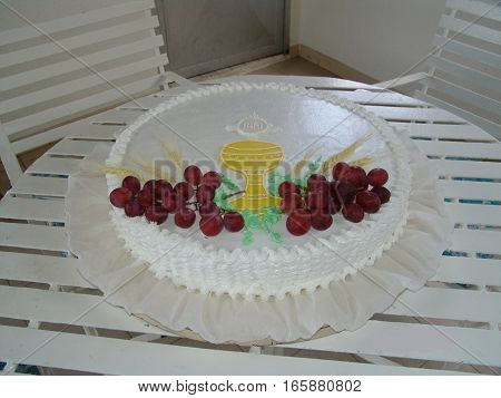 A first communion cake with grapes and calyx.