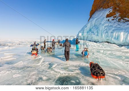 Lake Baikal Russia - March 24 2016: Group of tourists adults and children is on the ice of Baikal with the sledges ice transition in the March 24 2016