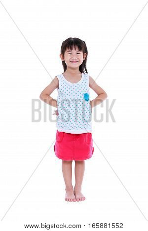 Full body of happy asian child posing in the studio, on white background. Playful girl smiling and looking at camera. Studio shot.
