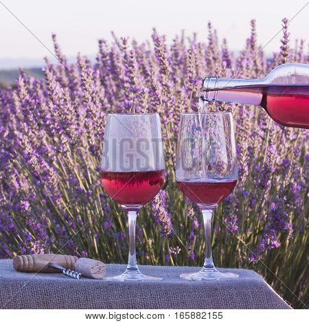 A vibrant square photo of rose wine being poured into glasses in a lavender field. The glasses are on a crate with a burlap texture, with a retro corkscrew and a cork. Slightly toned image