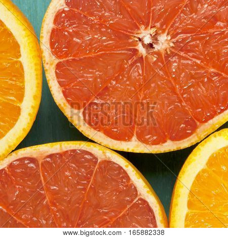 A square macro photo of vibrant grapefruits and oranges, cut in halves, shot from above
