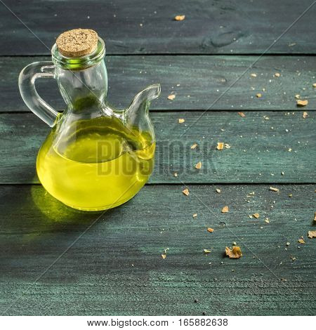 A square photo of a pitcher of olive oil on a wooden board with bread crumbs and copyspace