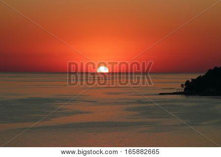 Beautiful sunset on the sea coast. Bathing and fishermen