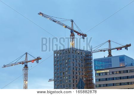 STOCKHOLM - JAN 15 2017: Sihouette of yellow cranes blue sky and high buildings. January 15 2017 in Hagastaden Stockholm Sweden