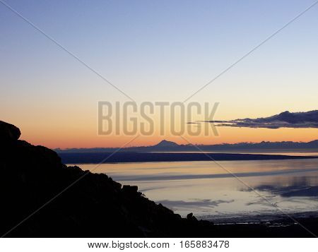 Amazing view of land silhouetted against an Alaska sunset or sunrise. Beautiful summer or spring morning watching the sun come up.