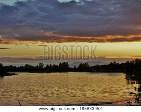 Beautiful sunset view reflecting on the water in Anchorage Alaska. Landscape with orange and gold clouds in sky at dawn or dusk.