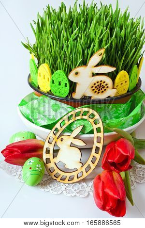 Traditional Czech easter decoration - green wheat seedings in the flowerpot and eggs with bunny decoration and red tulips on the white background. Spring easter holiday arrangement.