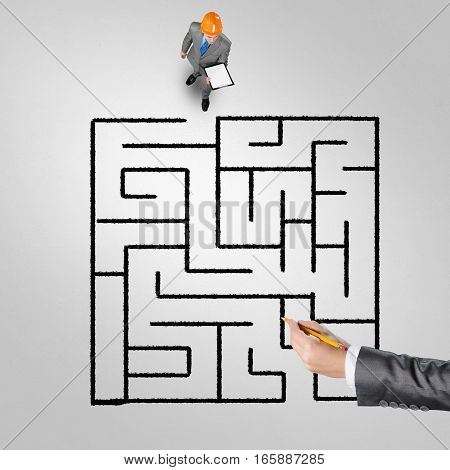 Top view of puzzled businessman in helmet looking at drawn maze on floor