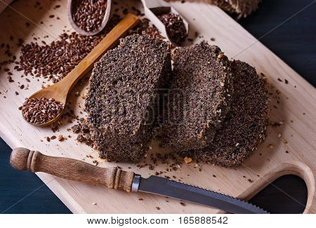 Grain free flaxseed bread slices on a cutting board over rustic wooden background