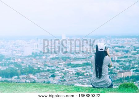 Woman sitting on the lookout City View shooting with the camera DSLR