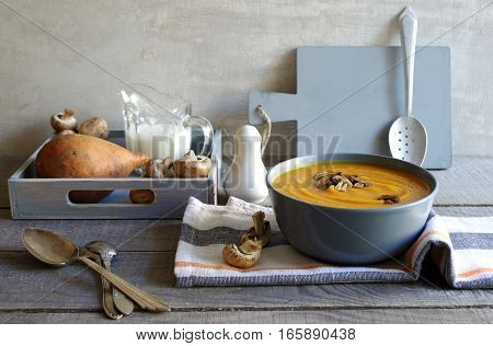 fresh homemade yam soup with roasted fungi in a grey bowl