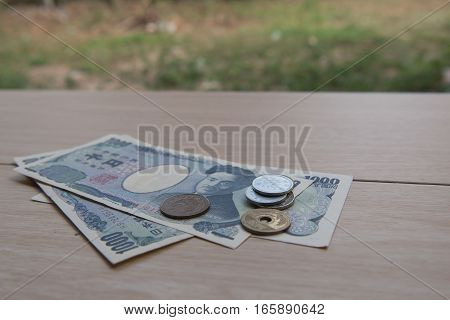 Closeup coin yen and banknotes Japanese  on wooden background. Currency of Japan.