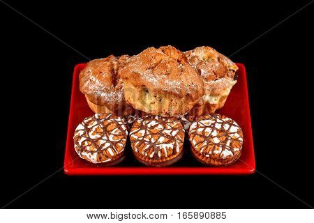 Cake and chocolate chip cookies on a red plate on a black background.