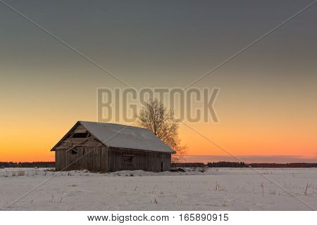 The midwinter daylight is fading away just a couple of hours after sunrise in the Northern Finland. A lonely barn house prepares itself for the darkness.