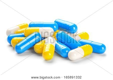 pills blue, yellow and light blue tablets on  white background