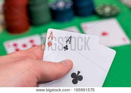 poker player holding play cards with chips and money