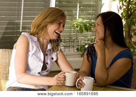 Happy multicultal women drinking coffee and talking