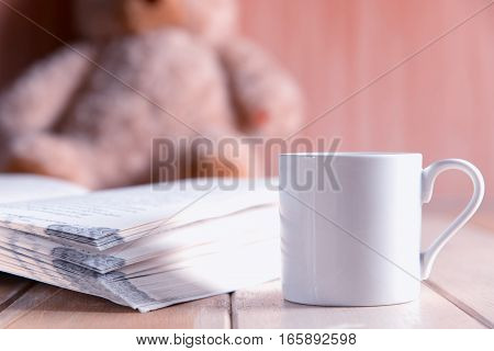 Coffee Cup And Book Focused On Teddy Bear In Blurred Background