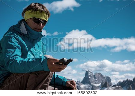 Portrait of hiker woman with GPS navigator in Alps mountains