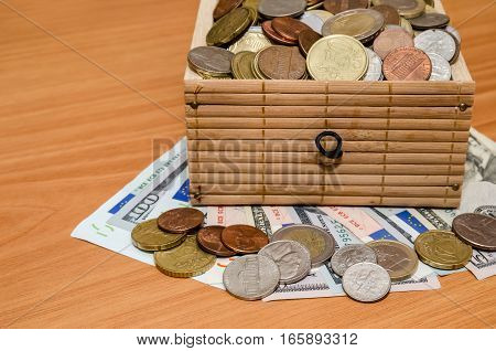 Dollar and euro money with coins in the treasure chest