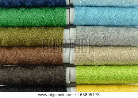 Closeup sewing threads multicolored background - green tone