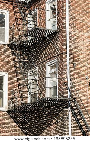 Fire escape iron ladders on old vintage brick wall building facade