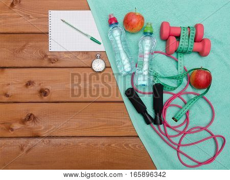 Fitness concept with dumbbells towel apples bottle of water measure tape notebook and skipping rope on wooden table background