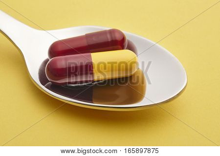 Pills and spoon detail. Yellow background. Medicament treatment. Health care photo