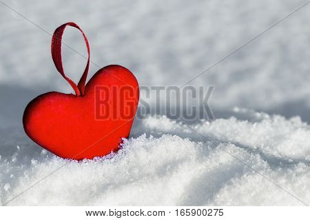 Red heart on the snow. Christmas decorations