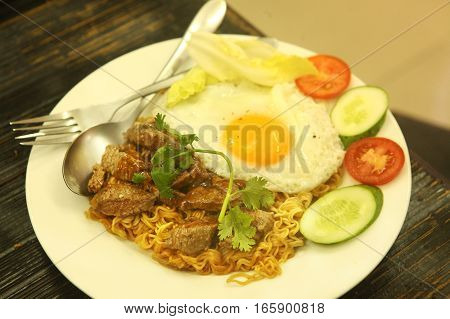 fried eggs served in frying pan with moodles beef cucumber and cut tomato