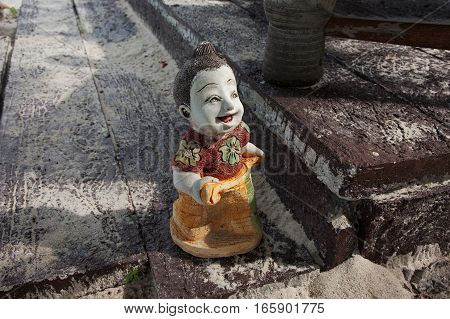 stone figurine on a wooden board in the park
