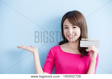 beauty woman hold teeth whitening tool isolated on blue background