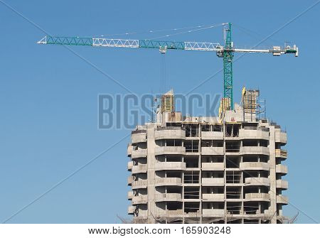 Big hoisting tower crane and top of construction building over cloudless sky