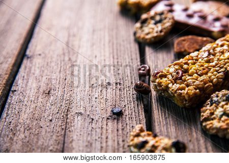 Set of sweets. Chocolate bars and granola on a wooden background with milk chocolates. Food candy snack