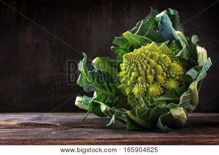 Romanesco broccoli or Roman cauliflower on a rustic table from dark wood the healthy vegetable Brassica oleracea is a variation of cauliflower bred near Rome copy space