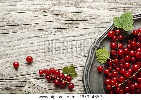 Fresh redcurrant on wooden background close up
