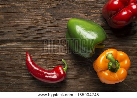 Green yellow and red bell pepper on wooden background