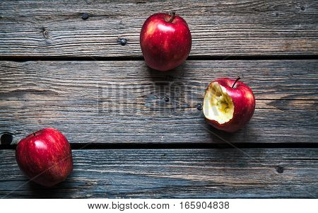 Fresh organic whole and bitten off apples on rustic wooden background. Selective Focus. Rustic style.