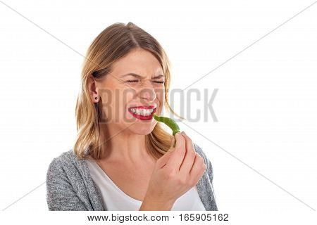 Picture of a young woman biting of a hot paprika