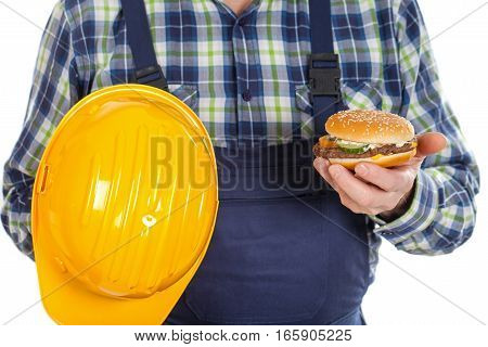 Close up picture of a male engineer holding his helmet and a tasty hamburger