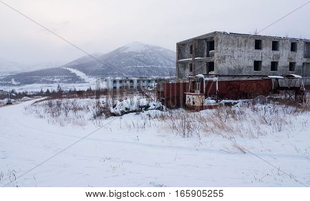 Abandoned settlement with decayed buildings and old destroyed bus in Kolyma winter view