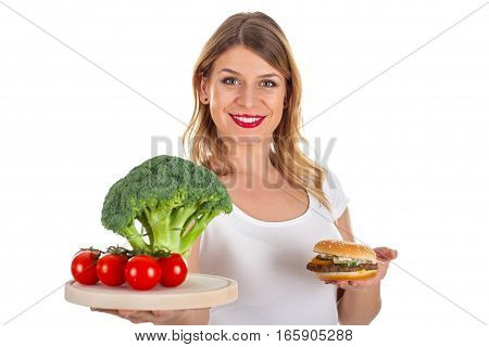 Picture of a smiling woman holding a hamburger and fresh vegetables