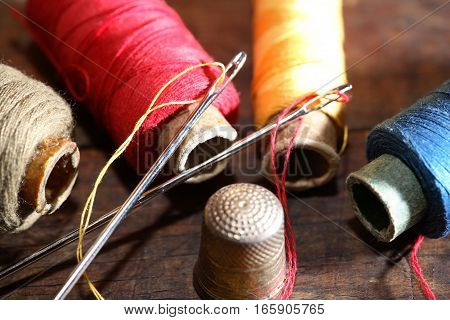 Thimble and needle near thread on old wooden background